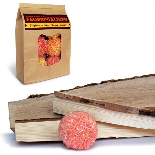 Stimmungbild von den side by side Feuerpralinen in der Verpackung - zusammen mit Brennholz.